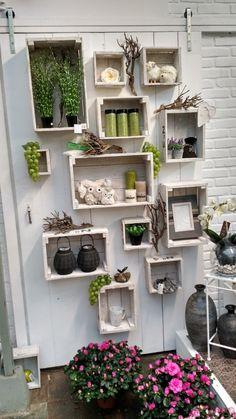 Leuk idee voor een kale tuinmuur: aparte kistjes waar je plantjes, lampjes etc. in en op kunt zetten.