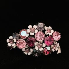 Stunning WEISS BROOCH This luscious WEISS brooch is a stunning combination of lavender, light pink and hot pink rhinestones, several of which are covered with aurora borealis. The flowers interspersed among the rhinestones are simply lovely. This brooch is in excellent vintage condition. Vintage Jewelry Brooches
