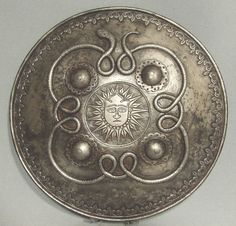Indo-Persian steel shield of Dhal Separ type, 1700s. Decorated with twining serpent and a central face. Scroll work around rim.