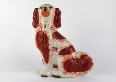 An antique porcelain Spaniel figurine. English Staffordshire, glazed in white and rust red. from EBTH.com