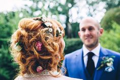 pinned bridal curly up hair do with fresh flowers - Image by Mister Phill - A vintage dress with a bespoke cape for a brightly coloured festival, country fete themed wedding on parent's property with an outdoor ceremony.