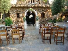 Weddings in Crete - Wedding Arch and Taverna Wooden Chairs with White Ribbon Bows