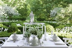 In a garden setting, the table is set in monochromatic white featuring stark white porcelain and delicate lily of the valley. Carolyne Roehm
