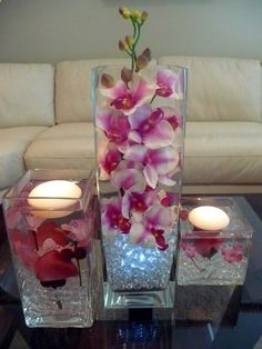Pairing square clear glass vases, vase fillers, floating candles  flowers create candle decor, so cute!