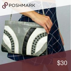 Vintage 80's Retro Leather Studded Clutch This retro clutch features a funky bold pattern of black, grey, and white color blocks. Accented with black studs and gold-tone hardware. It has a removable strap to transform it from a clutch to a shoulder bag. Has a zip closure, an interior zip pocket, and a snap closure pocket on the front.  1980's  Good pre-owned condition, signs of wear on leather shown in pictures.  Dimensions: 8 inches tall, 11 1/2 inches across, 26 inches from strap to bottom…