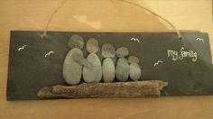 Beach pebble family Sat on a drift wood branch on a thick slate tile xx