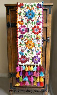 Corredor de lana de oveja mano bordada con flores elegantes y hojas, acabado con borlas multicolores. Magnífico en su mesa o como un corredor de la cama. Los colores vibrantes y motivos detallados hará cualquier habitación lucir hermosa! Las fotos son del elemento real que recibirás! Tenga en cuenta que las variaciones de color y pequeñas imperfecciones son naturales en artículos hechos a mano. Medidas 72 largo x 12 pulgadas de ancho Color crema