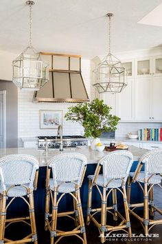 Serena & Lily Riviera Stools sit in front of a kitchen island painted in Benjamin Moore Hale Navy accented with white macaubas quartzite countertop fitted with a sink positioned under satin nickel gooseneck faucet illuminated by Suzanne Kasler Morris Lanterns.