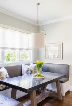 Breakfast nook boasts a built-in U shaped banquette with beadboard trim lined with a gunmetal gray vinyl cushions facing a trestle dining table illuminated by a cage drum pendant.