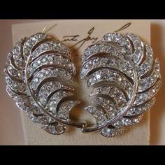 """Kenneth Jay Lane clip on CZ feather earrings Kenneth Jay Lane clip on CZ feather earrings, silver. Never worn. 2"""" in size. No trades, please. ****BONUS: by purchasing you are contributing to the """"my abusive ex husband almost ruined me and therefore help me find my footing"""" fund. Warm fuzzies! Kenneth Jay Lane Jewelry Earrings"""