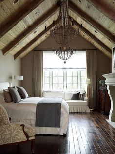 Vaulted ceiling with wood liner and beams. White furniture  and fireplace make a nice contrast to the rustic feel of the ceiling. The large wrought iron chandeliers are light and airy.