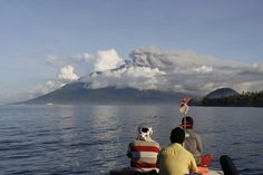 Fishermen look at Mount Gamalama as it spews ash into the air during an eruption at Ternate, Maluku island. Indonesia temporarily closed a domestic airport after a volcano in the country's east erupted, spewing plumes of ash hundreds of meters into the air.