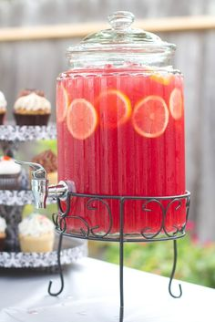 Pink Lemonade Sparkling Punch: 4 cans of frozen lemonade concentrate,  1/2 gallon of cranberry juice,1 46oz of red fruit punch Hawaiian punch recommended,1 quart of chilled Ginger Ale,1 46oz can of pineapple juice, 2 lemons thinly sliced, Ice