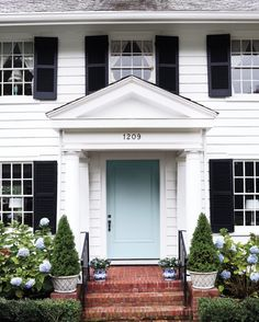 """Not only do the painted door and the """"Nikko Blue"""" hydrangeas flanking it give the Raus' home curb appeal, but they also hint at the palette that unifies the interior of the 1919 house."""