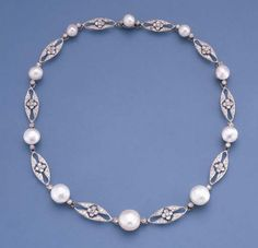 A BELLE EPOQUE PEARL AND DIAMOND NECKLACE  Comprising ten graduated button pearls measuring 7.2 to 14.3 mm. in diameter flanked by diamond collets to the marquise-shaped floral diamond spacers, millegrain setting, circa 1910