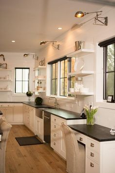 Beautiful kitchen features shiplap walls lined with white cabinets paired with soapstone countertops fitted with a stainless steel apron sink under a window flanked by stacked floating shelves. Soapstone Counters, Soapstone Kitchen, Dark Kitchen Cabinets, Kitchen Countertops, White Cabinets, Dark Counters, Black Countertops, Kitchen Island, White Floating Shelves
