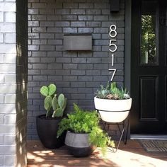 Porch plants and house numbers. Black exterior.