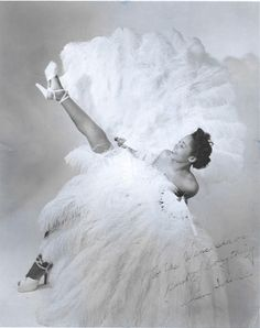 """Jean Idelle with her feather fans    """"Jean Idelle was one of the most sort after Exotic Dancers of her time. Ms. Idelle studied dance at the Katherine Dunham School of Dance in New York City. After a brief stint in Dunham's experiemental troupe, Ms. Idelle was discovered and made a headliner for Minsky's Burlesque Shows between 1950 to 1964. Ms. Idelle made her mark by performing in White and Black Shows across the U.S. and Canada"""