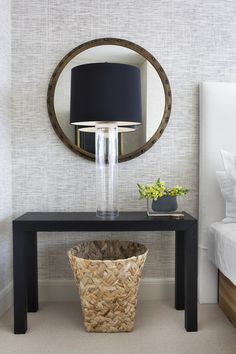 A bedside table with a glass-column lamp and a round mirror