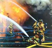 Firefighters sits on the ground to control the high velocity of the water hose