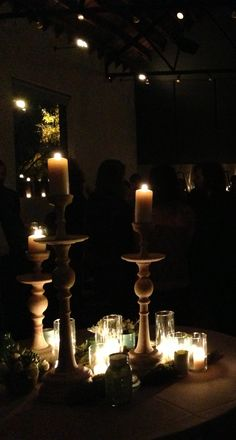 Candles cluster at a wedding reception evokes a old church at night.