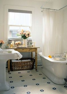 antique furniture in the bathroom under the window with towel storage basket underneath.