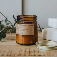 P.F Candles are a cult brand of natural soy wax candles housed within stylish brown jars. Teakwood & Tobacco is their best-selling fragrance.Handmade in America, Teakwood & Tobacco is their best-selling fragrance; a bold and complex musky scent. We stock five other scents.Burn time: 40-50 hours. Top Notes: orange leather, tobacco, amber, musk. Heart: black tea, pepper. Base: sandalwood, teak, patchouli. Essential Oils: cedarwood, patchouli, black pepper. 7.2 oz. D:2.75 X H:3.75 inche...