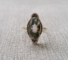 This Stunning Rare Antique Ring Features a Filigree Yellow 10k Gold Setting. Set with .20 Carat Natural Opal and a 2.38 Carat Jade Camphor.