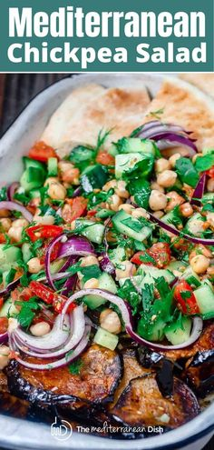 My family's secret Mediterranean chickpea salad, loaded with crunchy veggies, fresh herbs, and a tangy garlic and lime dressing! You can add your favorite entree or a side of cooked eggplant (like in the recipe) for a healthy vegan meal. #mediterraneandiet #mediterraneanrecipes #chickpeas #chickpeasalad #vegan #salad