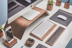 Side view of the walnut wood Grovemade Desk Collection with walnut wood monitor stand, leather and cork mouse pad, pen cups, desk lamps, planter, leather wrist pad, and keyboard tray.