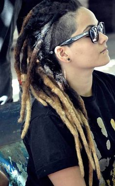 Dark brown dreads with blonde tips, shaved side, and some white paint