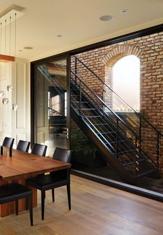 Architect Howard Airey and interior designer Alanna Johnston worked together to create a space made for entertaining in this Vancouver home, including a metal staircase that leads to the rooftop patio. The utilitarian feel of the staircase is mirrored by the exposed brick wall. #Starcase #WesternLiving