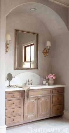 Classic Master Bath Twin vanities are tucked in arched niches. Cabinets were given a distressed finish and topped with marble