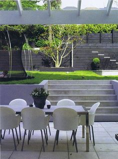 Concrete pavers, plaster block retained walls, black stained timber walls (and yes that's a sunken trampoline). Designed by Rach Matthews, Photo courtesy of NZ House Garden. Designed by Rach Matthews, HEDGE Garden Design Nursery