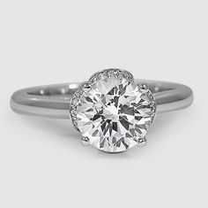 A dazzling center diamond emerges from four curving petals sparkling with diamonds on their tops and sides. The effect is at once nature-inspired and glamorous. #Capri #Jewelers #Arizona ~ www.caprijewelersaz.com  ♥