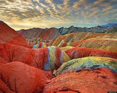 China's Danxia Landform Geological Park. These incredible colors are the result of layers of sandstone and various minerals.The mountains provide the vivid patterns.