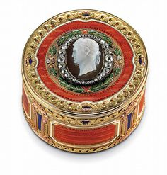 A Three-Colour Gold, Hardstone and Guilloché Enamel Box <br />Marked Fabergé, with the workmaster's mark of Michael Perchin, St Petersburg, circa 1890, scratched inventory number 45171<br />Circular, the sides enamelled with rectangular panels of translucent orange over a wavy guilloché ground within white enamel borders, alternating with lozenges of translucent blue enamel, the hinged cover set with an oval sardonyx cameo, finely carved with a bust of an emperor, possibly Alexander I, ...