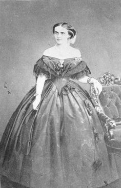 Crinoline evening dress: most evening dresses were off the shoulder necklines, sleeves were short, double skirts were used as decorative effects, trimmed with artificial flowers or ribbons, and closely fit at the waistline with a full skirt.