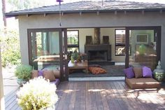 FAMILY ROOM with lots of windows and sliders onto deck area with extra seating - shaded by tall trees