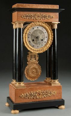 A VERY FINE FRENCH EMPIRE REVIVAL PORTICO CLOCK 19th century. The gilt bronze clock case with silvered dial suspended by ebonized columns raised on a birch base with gilt bronze floral mounts. Height 19.75 inches (50 cm).