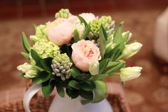 White parrot tulips, purple hyacinth, peach garden roses and green viburnum.