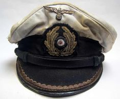 This is a reproduction of a Kriegsmarine U-Boat Captains Peaked cap with 70+ years of ageing and numerous oil stains and some worn areas.    The peak, liner and chinstrap etc. all show good wear and both the inside and outside are heavily oil stained and aged. Notice the gold emblem and Captains peak ranking are dark and tarnished.    There is also a wear and tear hole to the right hand side.