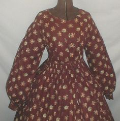"1860's Brown Floral Print Cotton Dress | eBay seller fiddybee; worn by member of Comb's family (name hand printed on inside of bodice) bell-shaped sleeves, piping at neck, dress all hand stitched, bodice lined with home spun linen, no hooks & eyes on front, skirt attached to waist w/ cartridge pleating, skirt unlined, period mend gussets under each arm using same fabric, bust: 35: waist: 32, skirt length: 39""; width at hem: 106""."
