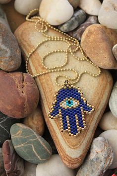 The Hamsa is a palm-shaped amulet popular throughout the Middle East and North Africa, and commonly used in jewelry and wall hangings. Beaded Flowers Patterns, Beaded Earrings Patterns, Beading Patterns, Bead Embroidery Jewelry, Beaded Embroidery, Bead Jewellery, Hand Jewelry, Handmade Jewelry, Bead Loom Bracelets