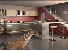 Une Cuisine ouverte sur salon en total look couleur taupe subtilement associée à une peinture rouge brique et des meubles chêne clair. Photo : SoCoo'c