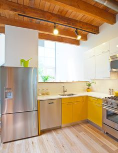 modern kitchen with yellow cabinets by Oakwood Projects Ltd.