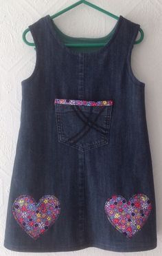 Upcycled a pair of denim jeans into a girl's pinafore age 3. Added appliqué hearts & pocket for detail. Fully lined in contrasting colour, jersey knit fabric.