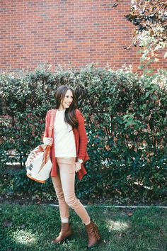 Chunky orange sweater with brown skinny pants and brown fringe booties