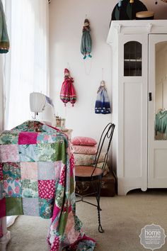 Farmhouse fancy: the inviting spare bedroom features a large vintage wardrobe from Rabbit and Hares, while exotic clown dolls from Thailand make a colourful display on the white walls.