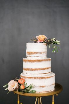 naked wedding cake with a dusting of frosting